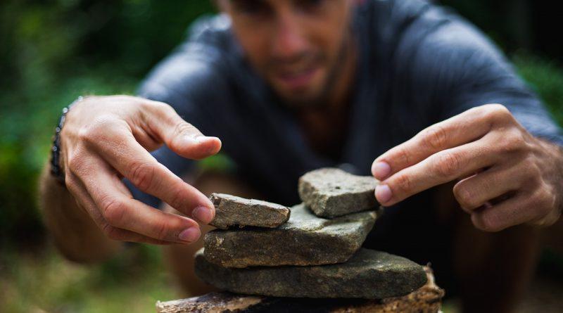 Ein Mann der aus Steinen eine Pyramide baut: einfach oder nicht?