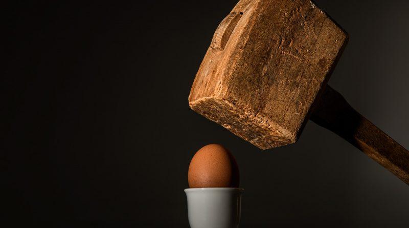 Ein Hammer schwebt über einem Ei