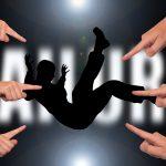 Schatten einer Person, die fällt und auf die alle mit dem Finger zeigen